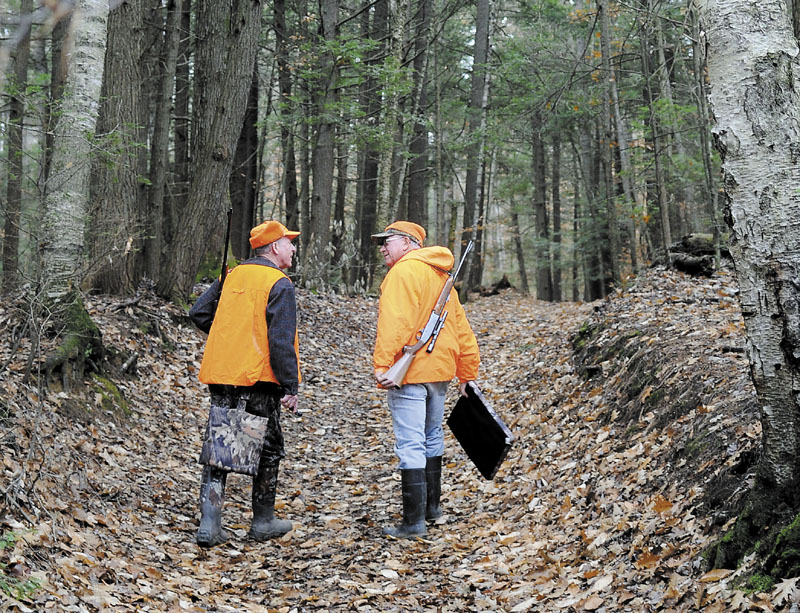 "Staff photo by Andy Molloy DEER ARE: Bill Moulton, right, of Pittston, chats with his pal, Gary Alexander, of Gardiner, as they walk down a path in a wood in South Gardiner in pursuit of Whitetail deer. Moulton said the men have been hunting together ""for about 68 years."""