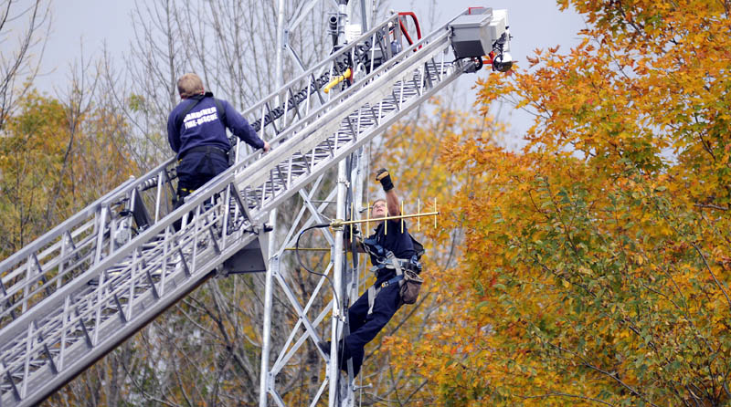 Staff photo by Andy Molloy TUNING IN: Gardiner firefighters Rick Seiberg, right, and Josh Johnson hang communication devices on the City of Gardiner's new public safety antenna Tuesday at city hall.