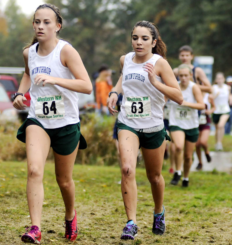 RUNNING IN A PACK: Winthrop High School's Molly Kieltyka, left, and teammate Kaitlin Souza compete on a muddy course Wednesday during a cross country meet at Monmouth Academy.