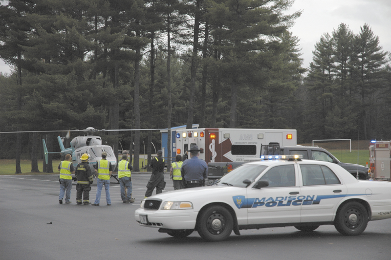 "A LifeFlight of Maine helicopter arrives Wednesday afternoon at a Madison High School parking lot to airlift Kerry Hebert, of Starks, to Central Maine Medical Center in Lewiston. Herbert was shot Wednesday in a possible ""hunting-related incident,"" according to police."