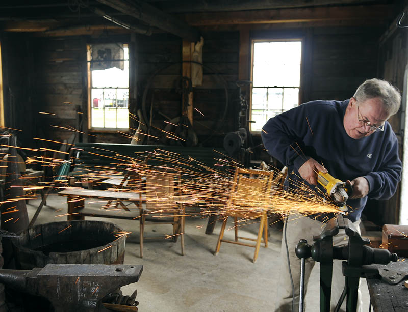 MANDREL MAKER: Bill Forbes brushes a mandrel Tuesday he created in the foundry of the blacksmith shop located on the grounds of the Windsor Historical Society. Forbes said he hopes to assemble the handle and blade of the axe with the new mandrel this week.