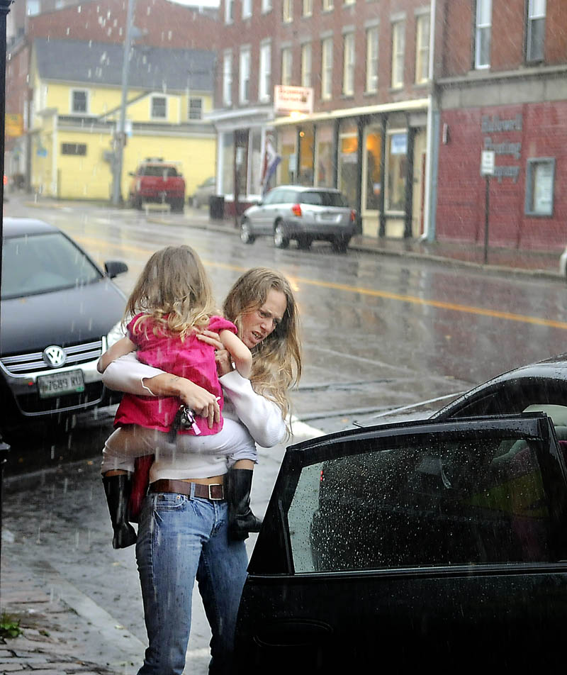 Dawn Lebourdais, of Gardiner, carries her daughter, Sivanna, 4, through a downpour Tuesday in Hallowell. Several inches of rain fell throughout Maine from remnants of superstorm Sandy.
