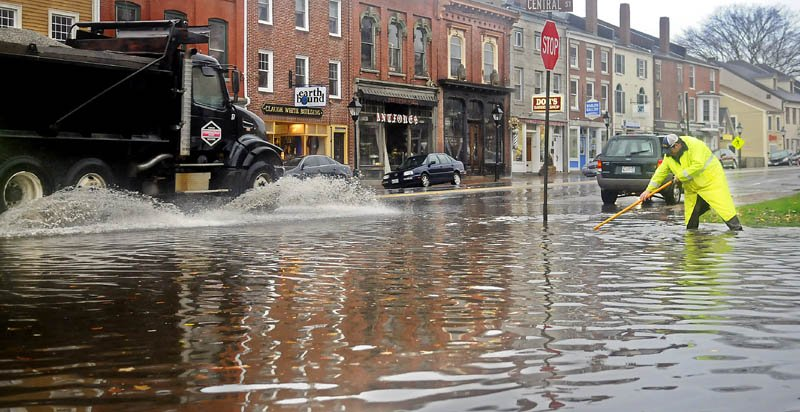 Hallowell public works employee Chris Buck clears a flooded storm drain Tuesday at the intersection of Central and Water Streets. Leaves displaced by superstorm Sandy plugged gutters and drains across Maine.