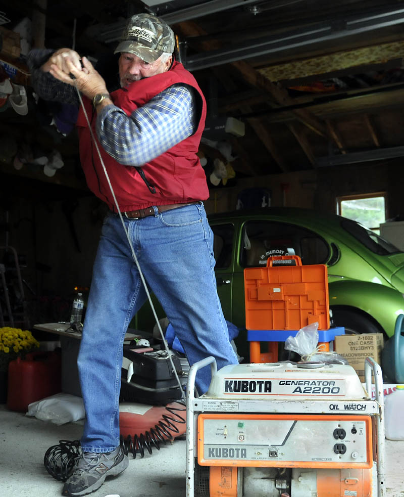 Carroll Whitman attempts to start a generator Monday belonging to his sister, Harriet Blanche, at her Manchester home. The siblings were preparing for the high wind generated by Hurricane Sandy. Whitman, a mechanic, said the mobile electricity supply can be tough to start if they aren't used often.
