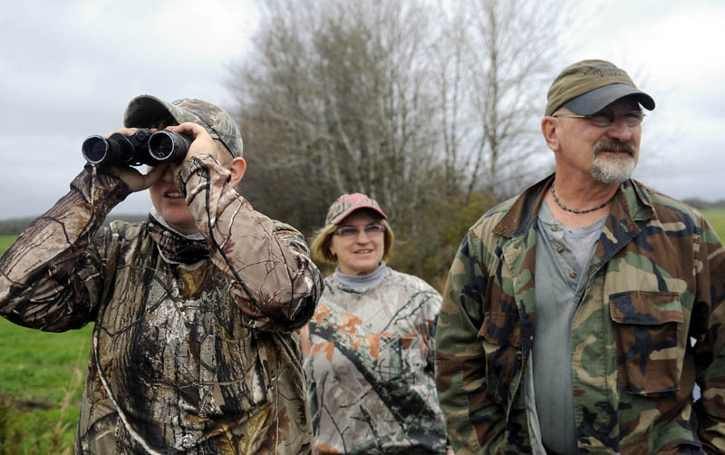 COVERT: Felicia Bell, left, of Richmond, Louis Chase and her husband, Rodney, of Bryant Pond, scan a field Monday for wild turkeys in Richmond. The Chases were accompanying Bell on her first hunt for tom gobblers grazing in open spaces in Richmond. The fall turkey season opened Oct. 13 and concludes Oct. 19.