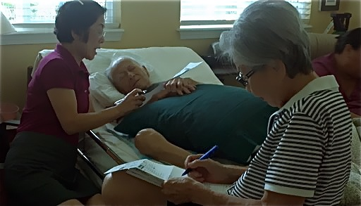 In this Oct. 17, 2012, photo provided by Irene Tanabe, Frank Tanabe, center, gets help from his daughter Barbara Tanabe, left, to fill out his absentee ballot in Honolulu while his wife Setsuko Tanabe sits in the foreground.