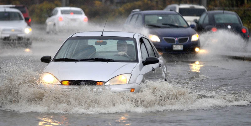 Drivers encounter flood water on the Waterville side of the Ticonic Bridge after heavy rains fell in Waterville Tuesday.