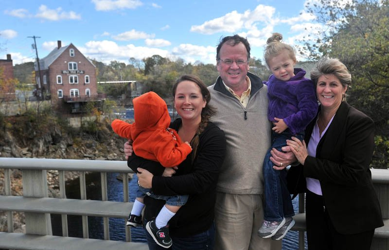 Greg and Paula Dore pose for a picture with daughter-in-law Christen Dore, left, and grandchildren Bentley, 1, and Marley, 4, on the Margaret Chase Smith Bridges with the Old Mill Pub in the background, on the left, in Skowhegan on Thursday.