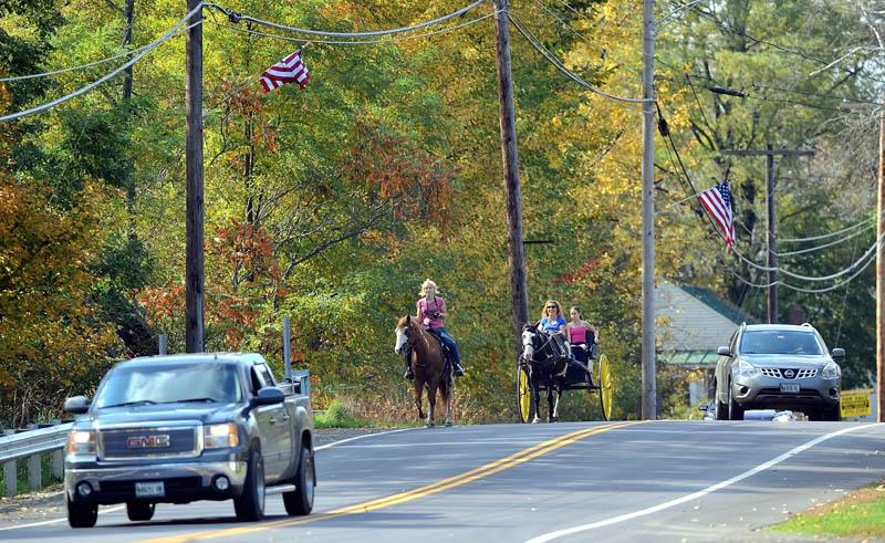 Charlene Bigelow, 18, rides her horse, Cider, as Alice Hadley drives her cart with Emily Fortier, 12, down HWY 16 in North Anson on Friday.