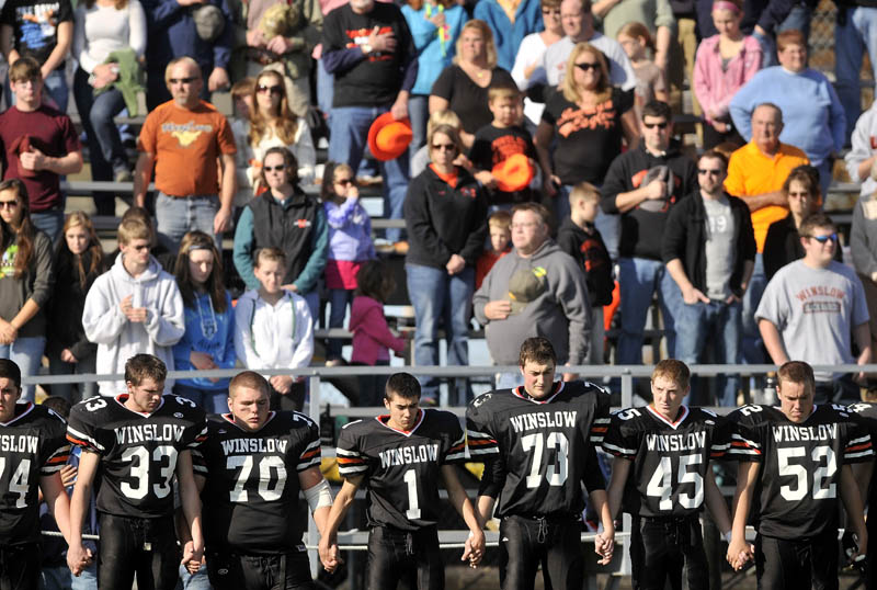 The Winslow High School football team holds hands during a moment of silence on Saturday, for two classmates killed in a car accident late Friday night.