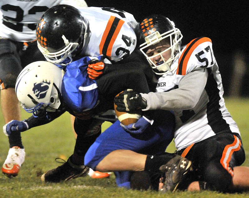 Staff photo by Michael G. Seamans Gardiner High School's Jory Vermillion, 57, right, and teammate seth Wing, 34, top, tackle Madison High School's Paul Dawe, 36, in the first half in Madison friday night.
