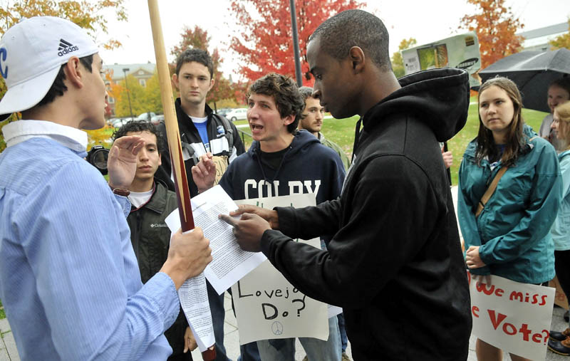 DEMONSTRATION: Colby College students Shelby O'Neill, center, and Uzoma Orchingwa, right, clash with fellow student Steve Carroll, left, outside the Diamond Building at the college during a protest against Bob Diamond protest organized by Occupy Augusta and concerned Colby College students on Saturday.