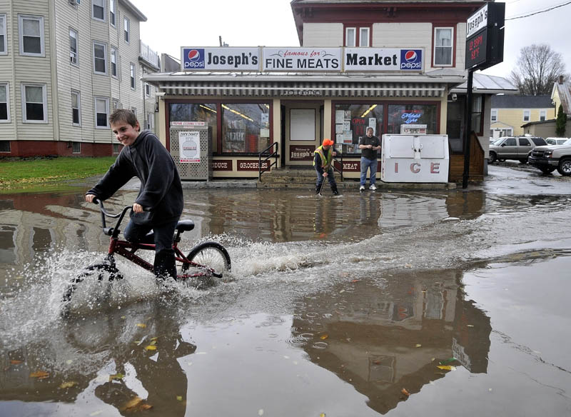 Hunter Desveaux rides his bicycle through flood waters on Front Street after heavy rains fell on Waterville Tuesday.