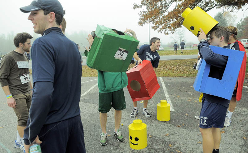 Colby College hockey players Ray, Ben Chwick, left center, Brendon Bourgea, right center, and Ray Zeek, right, get into their Lego costumes at the 4th annual Freaky 5k Run and Walk hosted by Hardy Girls Healthy Women and the Colby Volunteer Center at Colby College Saturday morning.