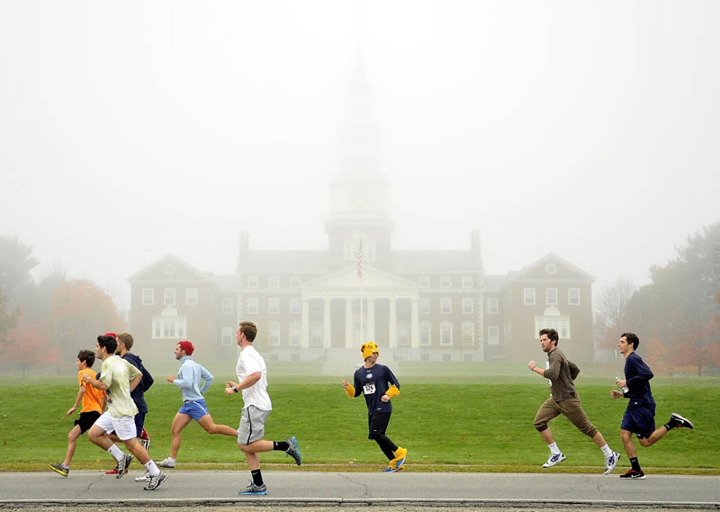 Participants in the 4th annual Freaky 5k Run and Walk hosted by Hardy Girls Healthy Women Colby Volunteer Center run down Mayflower Hill Drive in front of the Miller Library at Colby College Saturday morning.