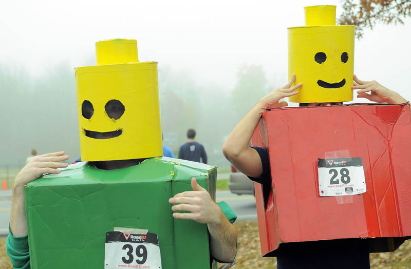 Colby College students Ben Chwick, left, and Brendon Bourgea, right, get in to their Lego costumes for the 4th annual Freaky 5k Run and Walk hosted by Hardy Girls Healthy Women and Colby Volunteer Center at Colby College Saturday morning.