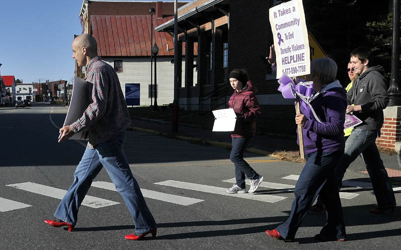Jon Heath, left, leads the 2nd annual Walk A Mile In Her Shoes march in a pair of red heels across Water Street in downtown Skowhegan Saturday morning. The march was organized to help raise awareness of domestic violence in Somerset County.