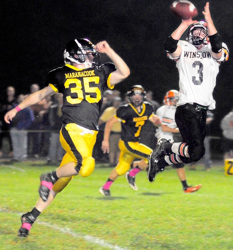Staff photo by Joe Phelan Maranacook linebacker Logan Emery, left, can't stop Winslow running back Dylan Hapworth from catching a long pass during a game Friday night at the Ricky Gibson Field of Dreams in Readfield.