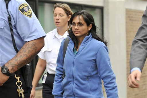 Annie Dookhan, center, leaves a Boston courthouse escorted by court officers and her lawyer. Dookhan is accused of faking drug results, forging signatures and mixing samples at a state police lab.