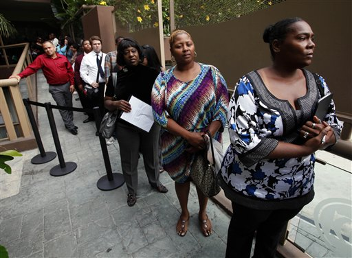 In this Aug. 17, 2012, photo, Sheila Bird, right, waits in line for employment interviews at a job fair at City Target in Los Angeles.
