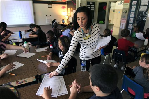 Kristine Nannini passes out student data sheets she created to her fifth grade class at McGrath Elementary in Grand Blanc, Mich., recently. Nannini spent her summer creating her own charts and student data sheets. It was something she imagined other teachers across the nation would want, so she decided to cash in on her prep time and sell her materials on teacherspayteachers.com.