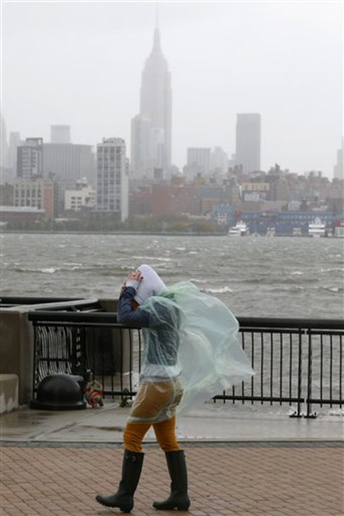 Heather Maschi, 24, tries to keep her hood on as gusty winds blow near the Hudson River on Monday in Hoboken, N.J.