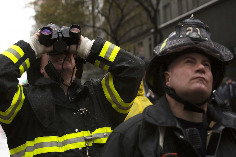 FDNY firefighters glare up at a damaged crane as it hangs over 57th Street after being torn from it's base by high winds, Monday, Oct. 29, 2012, in New York. Hurricane Sandy continued on its path Monday, as the storm forced the shutdown of mass transit, schools and financial markets, sending coastal residents fleeing, and threatening a dangerous mix of high winds and soaking rain.(AP Photo/John Minchillo)