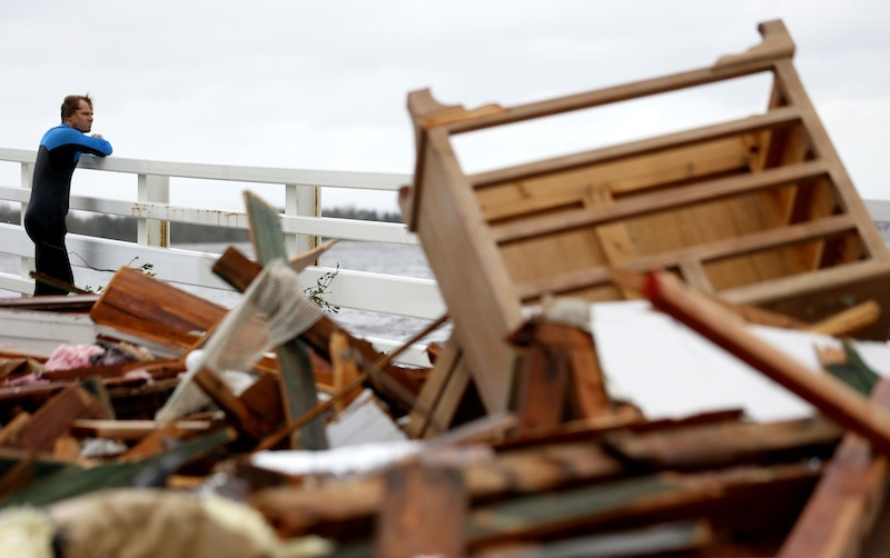 "Currie Wagner looks at the wreckage of his grandmother Betty Wagner's house, which was destroyed and wound up resting on top of the Mantoloking Bridge the morning after hybrid storm Sandy rolled through, Tuesday, Oct. 30, 2012, in Mantoloking. New Jersey Gov. Chris Christie said Tuesday that the devastation on the New Jersey shore is ""unthinkable"" and that the state will likely take months to recover. (AP Photo/Julio Cortez)"