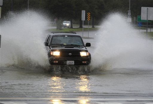 A car plows through a flooded street as rain and wind from Hurrican Sandy hit Norfolk, Va., on Sunday.