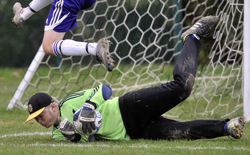 Staff photo by Michael G. Seamans Erskine Academy goalie Jared Gartley, makes a save as Waterville Senior High School's Michael Oliveira, 4, tries to get the rebound in the second half at webber Field in Waterville Friday afternoon. Waterville defeated Erskine 4-0.