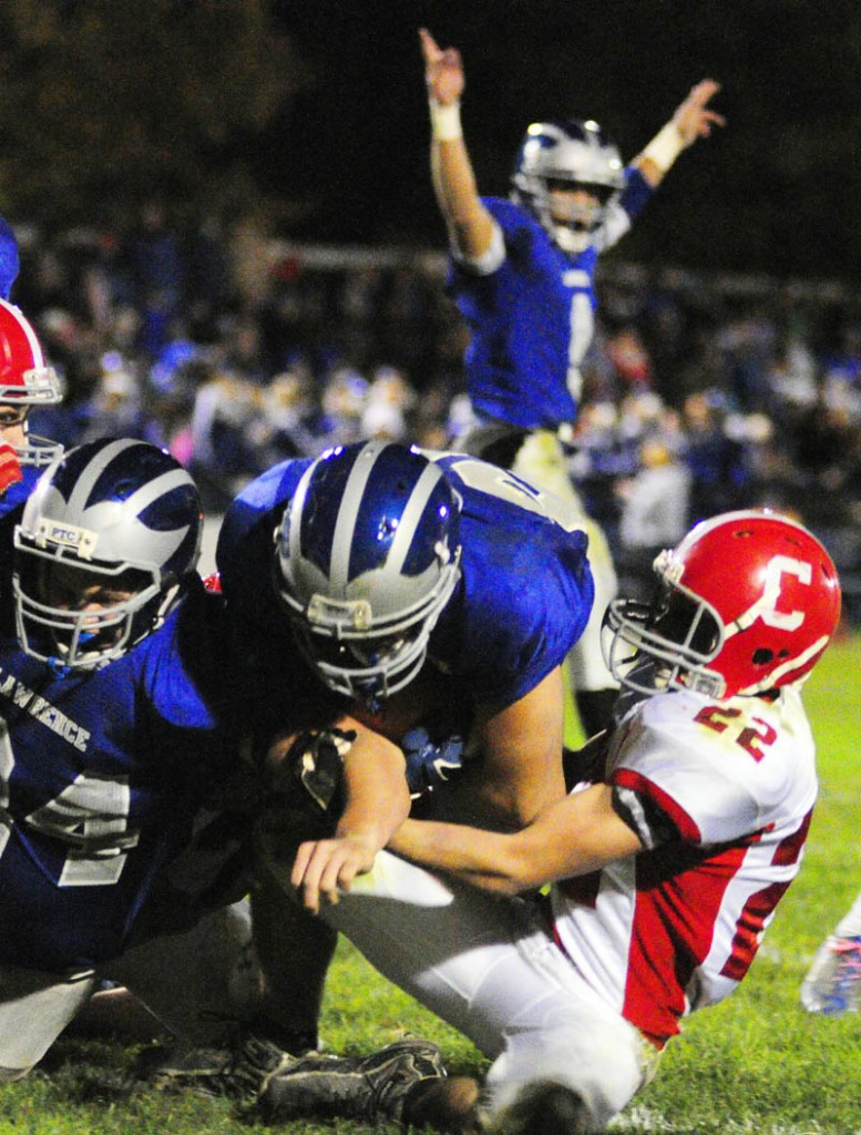 Lawrence's Jacob Gerow, left, blocks as Anthony Sementelli crosses the goal line with Cony's John Bennett, right, tries to stop him during a game on Friday night at Lawrence in Fairfield. Lawrence quarterback Spencer Carey, top, celebrates the Bulldog's third touchdown of first half.