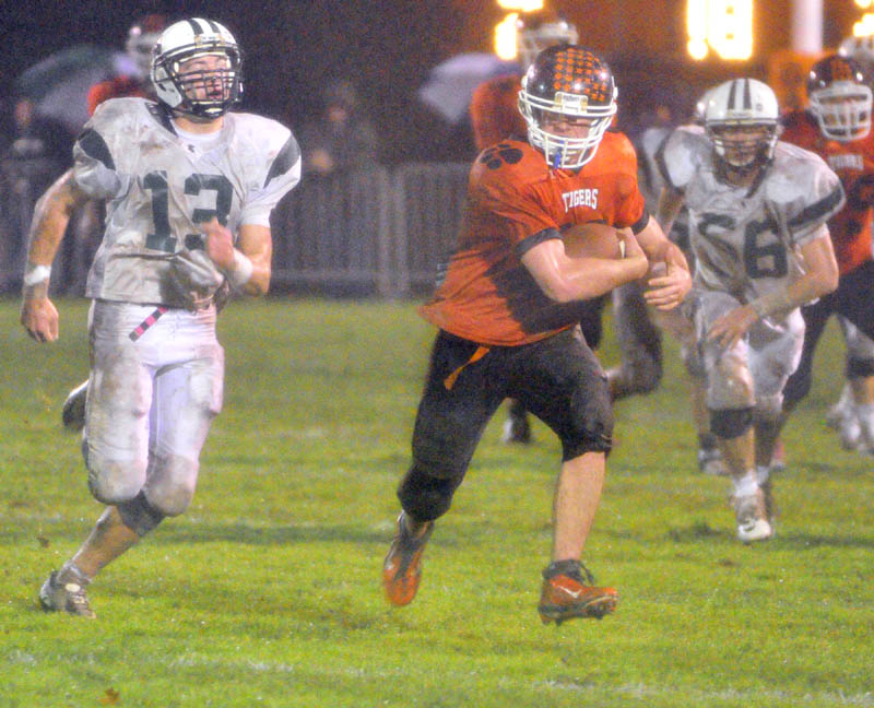 GAINING GROUND: Gardiner running back Steve Sirois, center, tries to outrun Leavitt defensive back Brian Bedard, left, and defensive end Brandon Collins during a game Friday at Hoch Field in Gardiner.