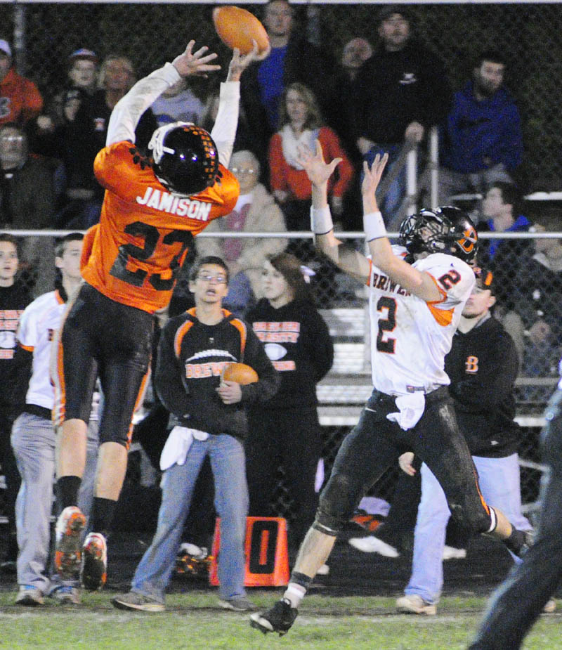 Gardiner's Tyler Jamison, left, tips a pass intended for Brewer receiver Spencer Valley during a game on Friday night at Hoch Field in Gardiner.