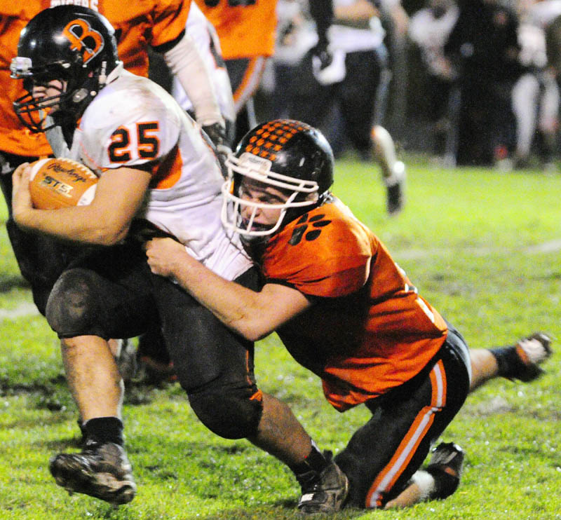 Brewer running back Dillon Smith, left, is dragged down by Gardiner defensive back Dennis Meehan during a game on Friday night at Hoch Field in Gardiner.
