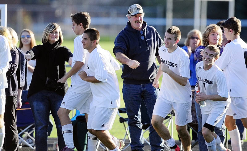 Hall-Dale players run back across the field after bumping fists with fans following a playoff game on Wednesday afternoon at Hall-Dale High School in Farmingdale. Hall-Dale defeated Lisbon 7-0.