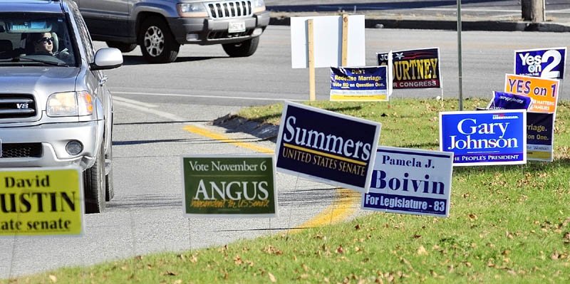 A driver looks at campaign signs while turning off Western Avenue onto Route 17 on Thursday afternoon, near the Manchester Town Office.