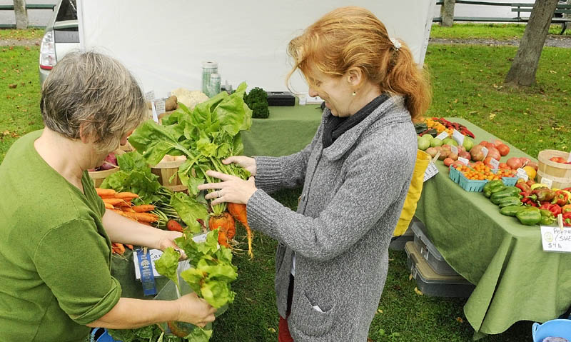 Laura Whatley, of Whatley Farm in Topsham, left, holds a bag open for customer Selma Holden, of Hallowell, to load up with golden beets on Wednesday afternoon at the Gardiner Farmers Market Wednesday afternoon on the Gardiner Common. The market is held there every Wednesday from 2 to 6 p.m.