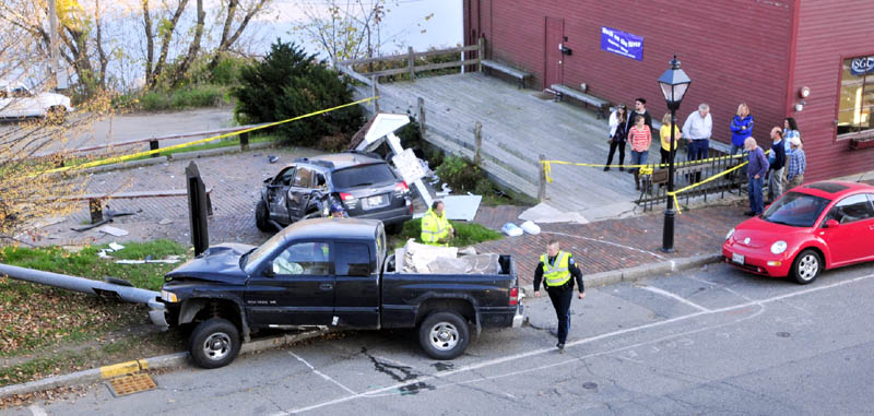 Hallowell police and firefighters clean up at the scene of an accident on this afternoon at the corner of Water and Winthrop Streets in downtown Hallowell. The pickup truck, front left, was traveling down hill on Winthrop Street when it struck a parked vehicle, top, which was then slammed into a sign board. The truck also knocked over a light post before stopping in the sidewalk. Two people in the truck were injured.