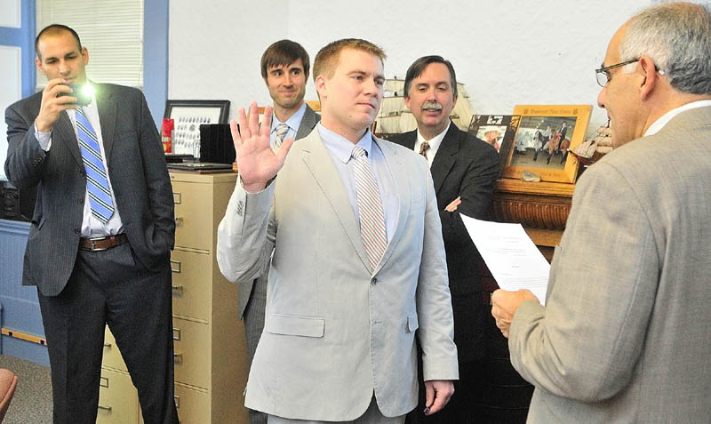 Francis Griffin, Jr., left, receives the oath of office as a new assistant district attorney in the Kennebec/Somerset district, from his uncle, Maine Supreme Judicial Court Associate Justice Joseph M. Jabar, on Thursday afternoon in Kennebec County Superior Court House in Augusta.