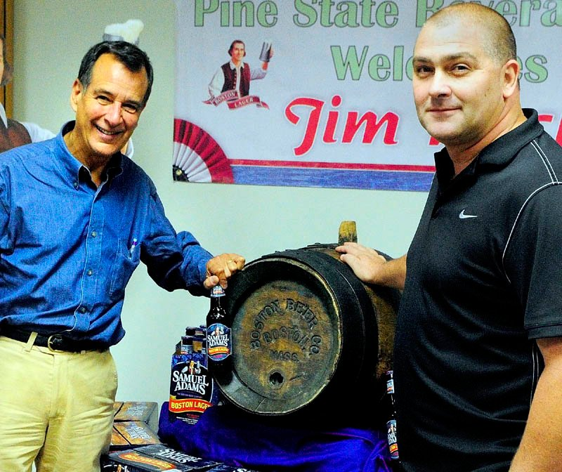 Jeff Damon, co-owner of Damon's Beverage Mart, right, donated this antique wooden beer keg to Jim Koch, left, founder of the Boston Beer Company and the maker of Samuel Adams beers.