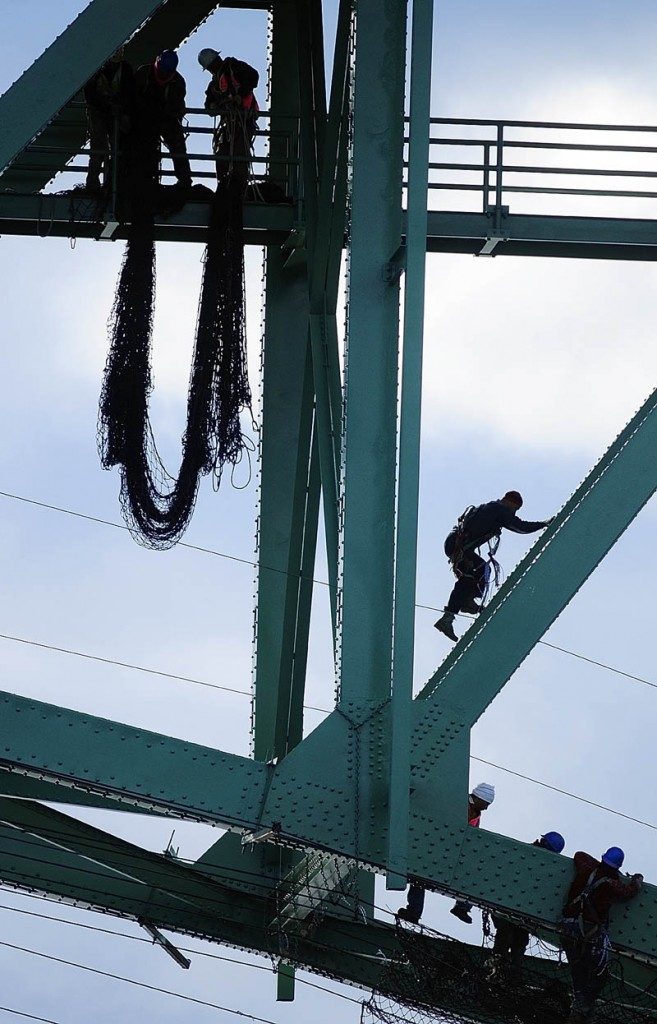 Staff photo by Joe Phelan Workers remove netting on Thursday morning from the underside of the Memorial Bridge over the Kennebec River in Augusta. The netting had been up over the summer during a recently finished paint job for the green bridge that carries US Routes 202 and 201 between the Memorial and Cony Circles.