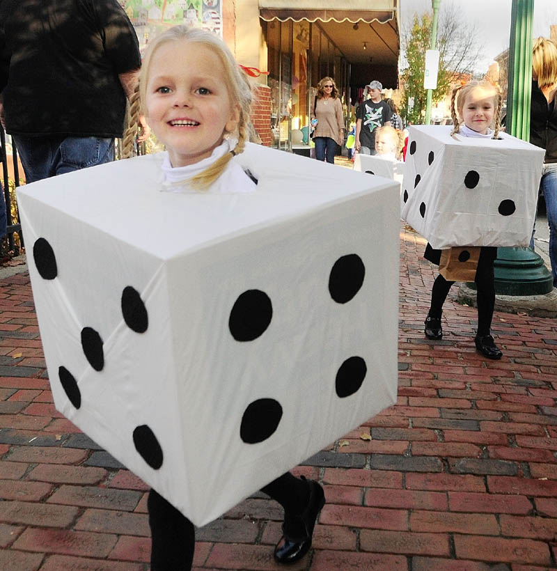 YAHTZEE: Hallee McCarthy, 3, left, leads her sisters Chloe, 4, right, and Taylor, 3 center, as the three girls from West Gardiner, walk down Water Street on Friday afternoon in downtown Gardiner. Hundreds of people were trick or treating at businesses on the street before a parade and costume were held.