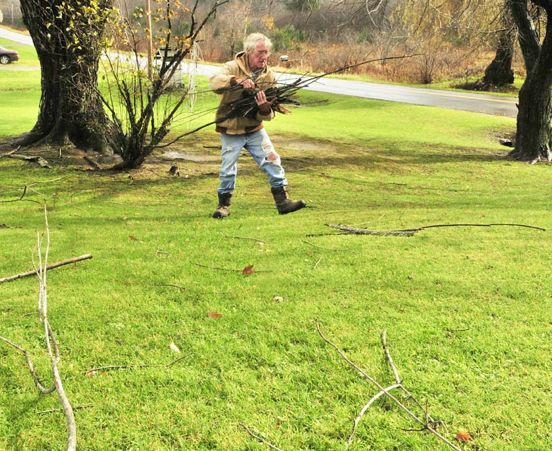 """Alfred Jones picks up sticks blown down by Superstorm Sandy on Tuesday afternoon in the yard of his Vassalboro home. """"Wasn't really that bad, could be worse,"""" said Jones. Jones said that he was trying to keep the yard cleaned up and looking good since he is trying to sell the place."""