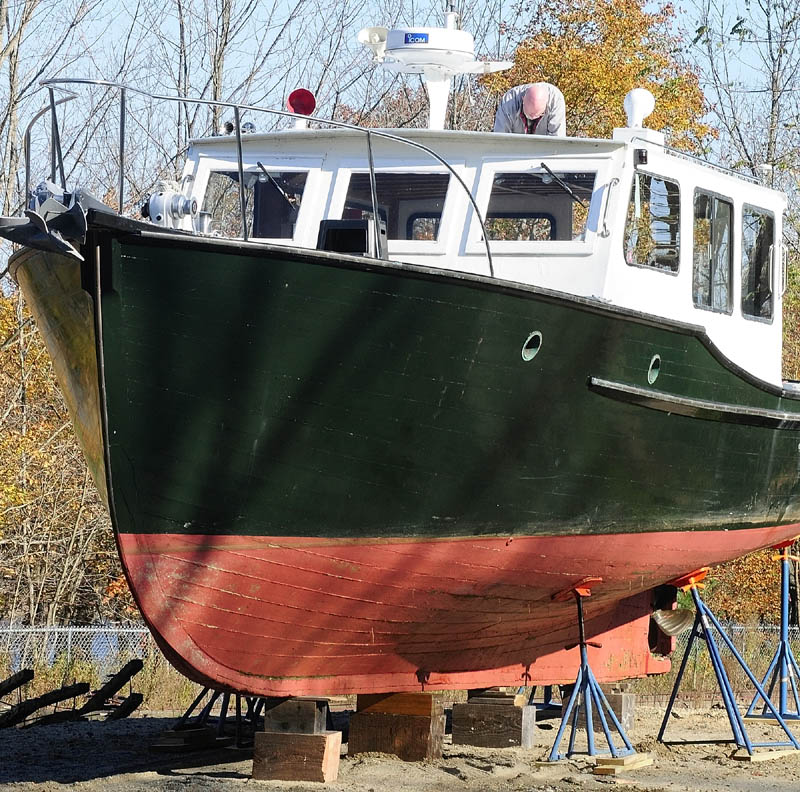 Jerry Maschino works on getting his boat Explorer ready for winter storage on Friday afternoon near his Gardiner. He said that she was built in Stonington in 1949 and had been moored over the summer in the nearby Kennebec River.