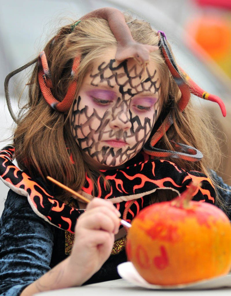 Staff photo by Joe Phelan Sedona Kmen paints a pumpkin during Halloween events on Wednesday afternoon at the Gardiner Farmers Market on the Common. Besides the the usual market stalls, there were face painting and games for the holiday.