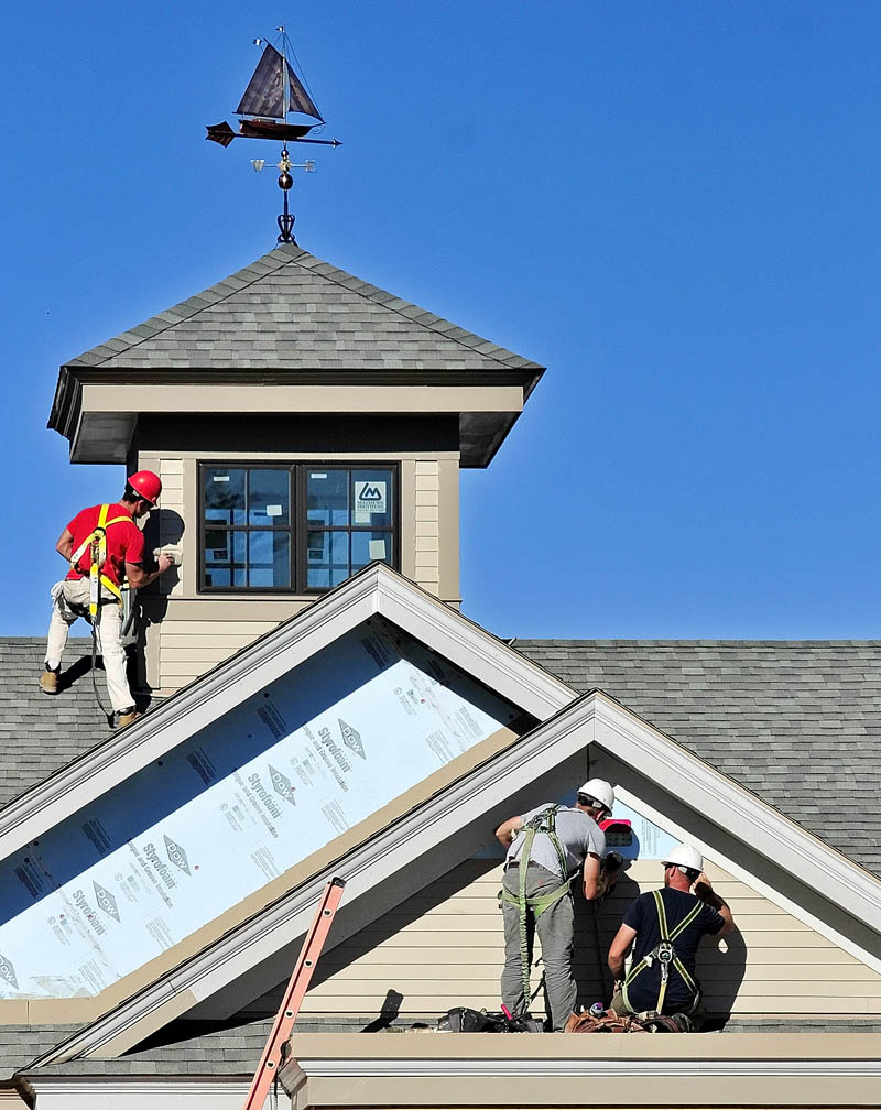 Workers paint trim and install siding on Thursday afternoon at the new Kennebec Savings Bank branch being built at the corner of Northern and Maine avenues in Farmingdale. The new building is designed to resemble the 1826 mansion that was removed earlier this year.