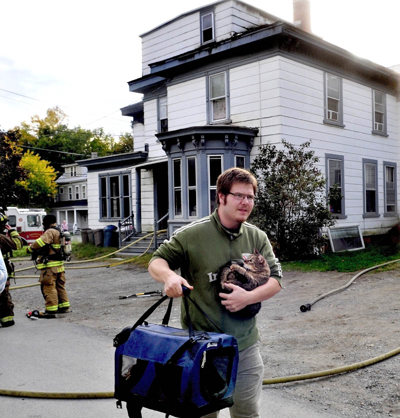 SAVED: Bill Laymon carries his cats Malcolm, in arms and Lenore, in bag, that firefighters rescued from the apartment, background, that sustained serious fire damage on Western Avenue in Waterville on Tuesday.