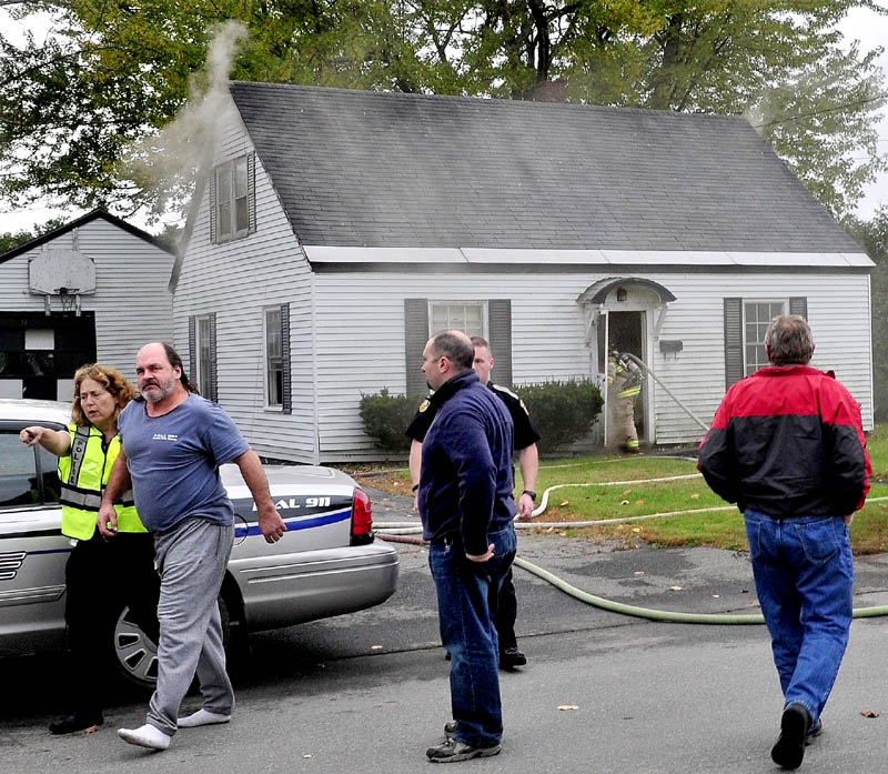 Tenant Jeff Macklin is escorted away from his burning home by Fairfield police officer Karen O'Donnell as firefighters enter the building on Military Avenue on Monday. Officer Jacob Pierce, background, entered the home and got Macklin out of the house.