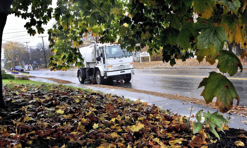 Tim Green of the Waterville public works department sweeps Upper Main Street clear of leaves and other small debris on Monday. The leaves could play a big part in flooding streets when hard wind and rain arrives for several days this week from Hurricane Sandy.