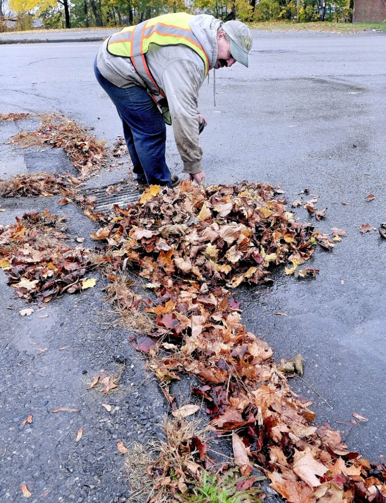 """STORM PREP: David Vigue of the Waterville Public Works department on Monday clears a drain full of leaves on Spruce Street ahead of the wind and rain expected from Hurricane Sandy. """"Our chainsaws are all gassed up to use for the next few days,"""" Vigue said."""
